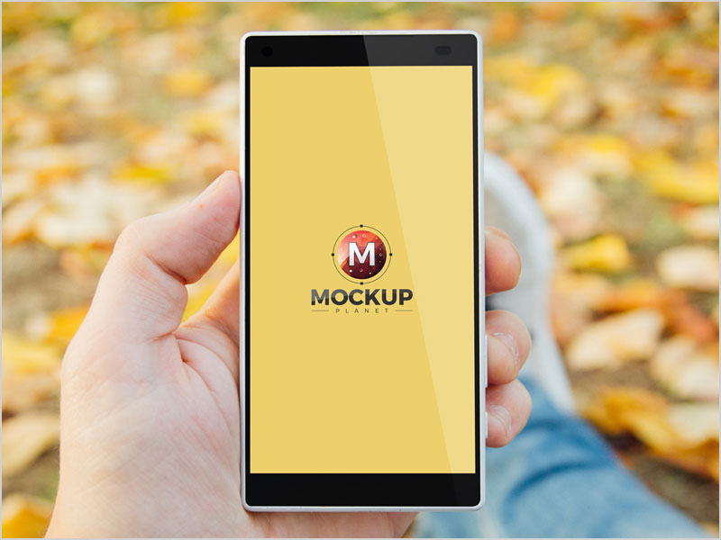 Free-Man-In-Park-Holding-Smartphone-Psd-Mockup